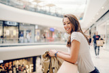 Smiling Caucasian charming brunette leaning on railing at shopping mall and looking away.