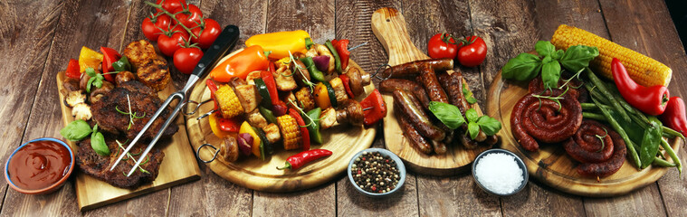 Assorted delicious grilled meat and skewer with vegetable on rustic table © beats_