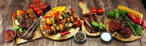 Assorted delicious grilled meat and skewer with vegetable on rustic table - 257677347