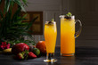 Mango lemonade - passion fruit in a jug and a glass and fruit on a dark wooden background