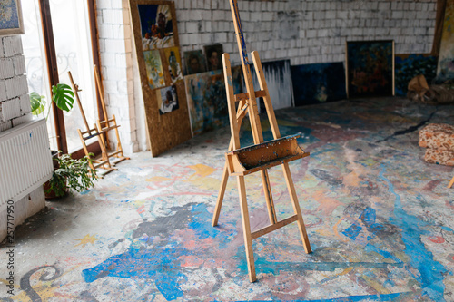 Close up photo of classic wood easel in modern cozy art workshop with colorful floor and window on background © Anton