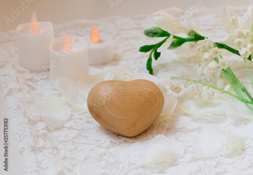 close up white romantic scene, wooden heart, candles  and flowers. © Corinne