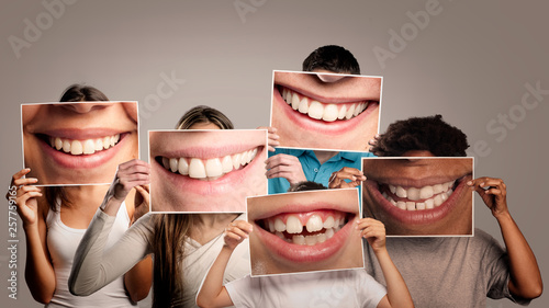 Leinwanddruck Bild group of happy people holding a picture of a mouth smiling on a gray background