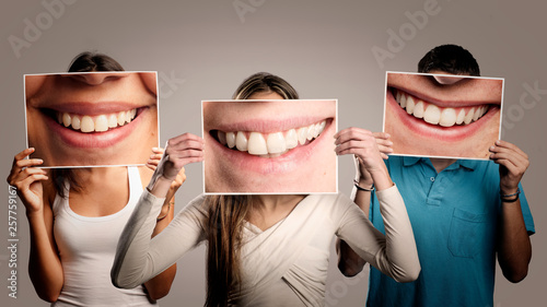 three happy people holding a picture of a mouth smiling on a gray background © xavier gallego morel