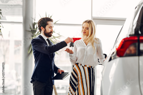 Woman buying the car. Lady in a car salon. Manager with a client © prostooleh