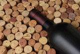 Closeup of a bottle of Cabernet Sauvignon wine surrounded by used corks