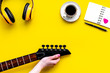 Musician work place with guitar, earphones, notebook and coffee on yellow background top view