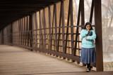 Hispanic Woman Praying And Holding Bible On A Bridge