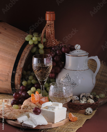 Red and white wine with cheese, nuts and grapes near the barrel on a wooden table © Pretti
