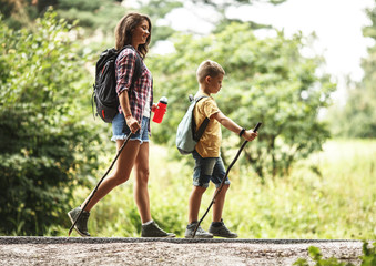 Mother and her little son hiking by the rural country road.Outdoor spring leisure concept.