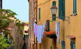Narrow street with view on the roofs and city lamp of old village Castiglione della Pescaia with laundry dry and old facade with windows. Grosseto Tuscany, Italy