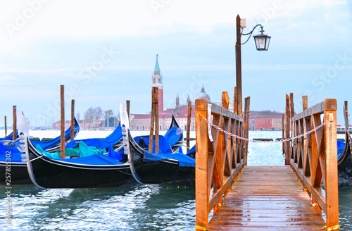 Gondolas moored on wooden dock by Saint Mark square with San Giorgio Maggiore church and island with cloudy blue sky in background  in Venice, Italy © poludziber