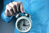 businessman holds an alarm clock