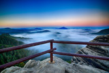 Fototapeta Fototapety na ścianę - Lookout view, wooden handrail fence on the rock. Hills with foggy morning. Twilight fall valley of Bohemian Switzerland park. mountains with fog, landscape of Czech Republic. Misty nature in Europe. © ondrejprosicky
