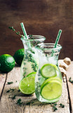 Ginger ale with lime, herbal cold summer drink with thyme and ice, vintage wooden table background, selective focus
