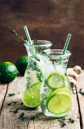Ginger ale with lime, herbal cold summer drink with thyme and ice, vintage wooden table background, selective focus - 257900948