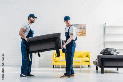 two movers in uniform transporting furniture in apartment © LIGHTFIELD STUDIOS
