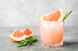 Leinwandbild Motiv Refreshing summer cocktail grapefruit rosemary juice and ice in glass goblet on a gray concrete background. Drink detox.