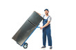 handsome mover in uniform looking at camera and transporting refrigerator on hand truck isolated on white