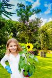 Beatifull girl with sunflower in the garden at summer day. Child relaxing in garden in sunny day. Little gardener playing in garden.