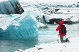Photographer in red coat taking pictures of glacier ice