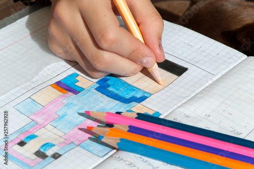 Child hand draws the multicolored minecraft picture.