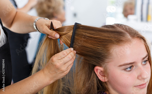 Leinwandbild Motiv Closeup of teen girl getting haircutting