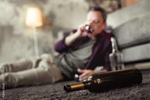 Adult man lying on carpet in living room with empty bottles around © Viacheslav Iakobchuk