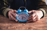 Elderly woman hands with alarm clock. Time