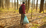 Fototapeta Fototapeta las, drzewa - The young guy holding big plastic bag with trash in the forest © SkyLine