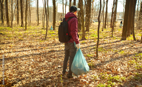 The young guy holding big plastic bag with trash in the forest © SkyLine