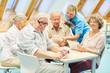 Leinwandbild Motiv Pflegekraft hilft Senioren im Computerkurs