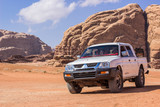 white car transport object in Wadi Rum Jordan Middle East scenery landscape with mountain background, rally and tour travel style concept photography