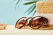 Leinwandbild Motiv selective focus of sunglasses and straw hat near seashell in summertime isolated on blue