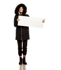 Young model in winter jacket with hood shows an empty advertising board on white background