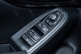 Сlose-up of the car  black interior:  the side door buttons: window adjustment buttons, door lock and other buttons.