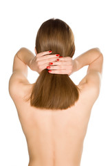 Back view of young nude woman holding her long hair on white background