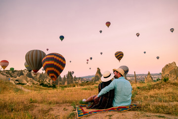 happy young couple during sunrise watching the hot air balloons of Kapadokya Cappadocia Turkey