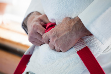 Hands of an elderly coach with a red-white judo belt and kimono.
