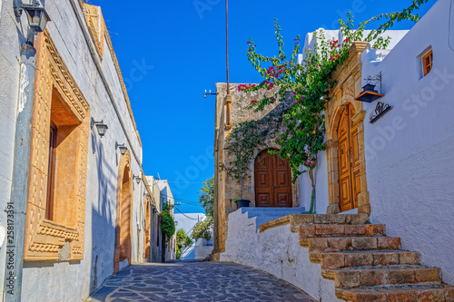 Beautiful scenic narrow wavy streets with ancient white houses and flowers. Famous tourist destination in South Europe.