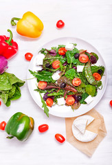 Salad in a white plate, cheese and vegetables on a white wooden background