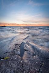Rock and waves in lake at sunset © Juhku