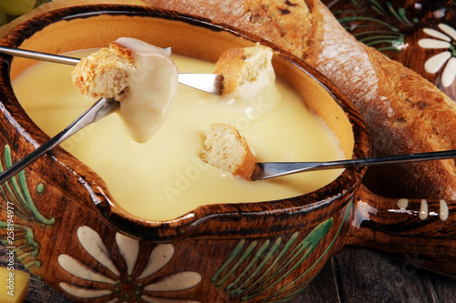 Gourmet Swiss fondue dinner on a winter evening with assorted cheeses on a board alongside a heated pot of cheese fondue with two forks dipping - 258194977
