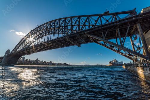 fototapeta na ścianę Sydney Harbour with sun shining through Sydney Harbour Bridge frame