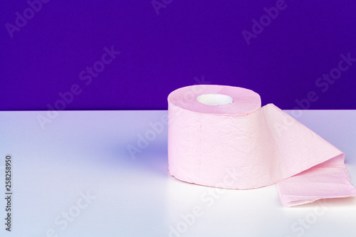 Toilet paper rolls isolated on white table with purple background - 258258950
