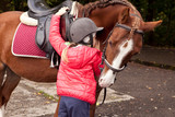 Fototapeta Fototapety z końmi - Girl on a pony in a helmet riding in the woods on a horse © Yury Fedyaev