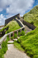 Biarritz, France. Atlantic ocean coast. Old stone stairs on slope of green hill. Sunny summer day © mikeosphoto