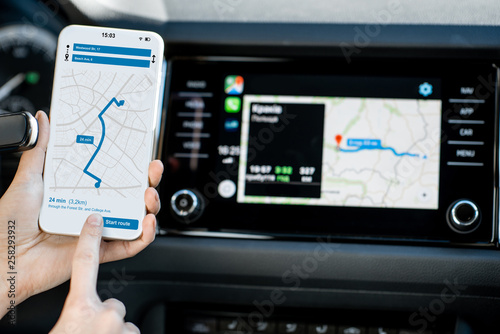 Close-up of a smartphone with navigation app in the modern car with monitor on the background