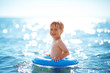 three years old boy playing at the beach with swimming ring