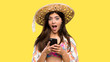 Leinwandbild Motiv Teenager girl on summer vacation surprised and sending a message over isolated yellow background